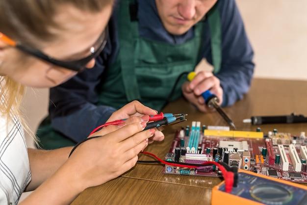Inżynierowie pracujący przy płycie głównej, naprawiający niektóre szczegóły