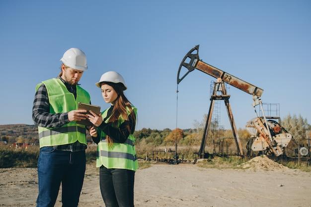 Inżynierowie pracujący w pobliżu jednostki pompującej olej. inżynierowie przemysłowi w twardych kapeluszach rozmawiają o nowym projekcie podczas korzystania z komputera typu tablet.