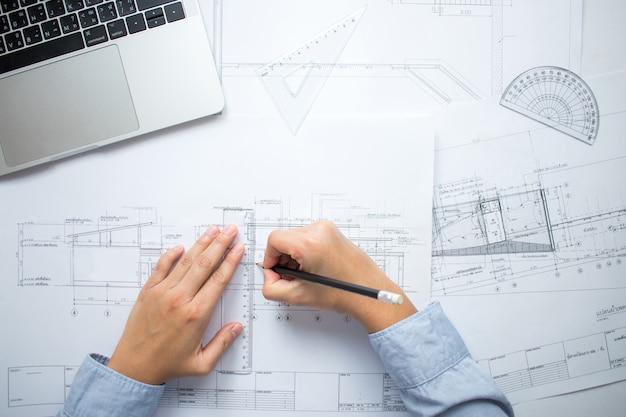 Inżynierowie rysują układ budynku na biurku.
