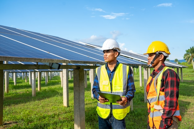 Inżynierowie sprawdzają i konserwują sprzęt w branży energii słonecznej, energii słonecznej, czystej energii, koncepcji wydajności i profesjonalizmu.