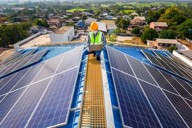 Inżynierowie używają laptopa do badania paneli słonecznych na dachu domu, w którym panele słoneczne są zainstalowane przy użyciu energii słonecznej.
