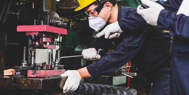Inżynierowie z fabryki metali w kasku, masce na twarz i rękawiczkach trzymają tablety do technicznej produkcji części metalowych za pomocą tokarek wewnątrz zakładu przemysłowego.