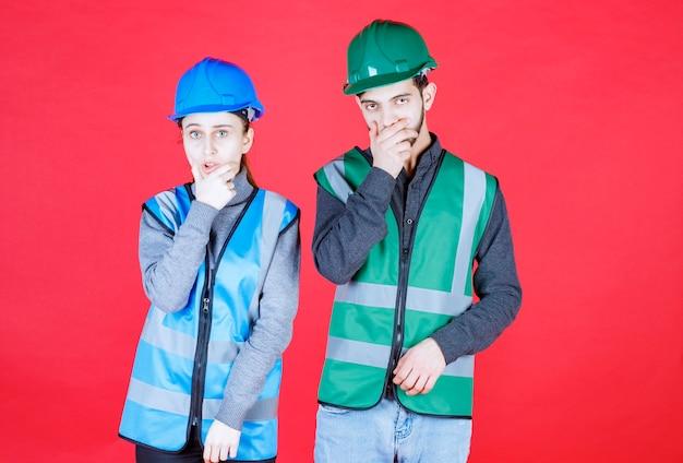 Inżynierowie z hełmami wyglądają na przestraszonych i przestraszonych.