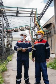 Inżynierskie podstacje elektryczne przeprowadzają przegląd nowoczesnych urządzeń wysokiego napięcia w masce w czasie pandemii. energia. przemysł.