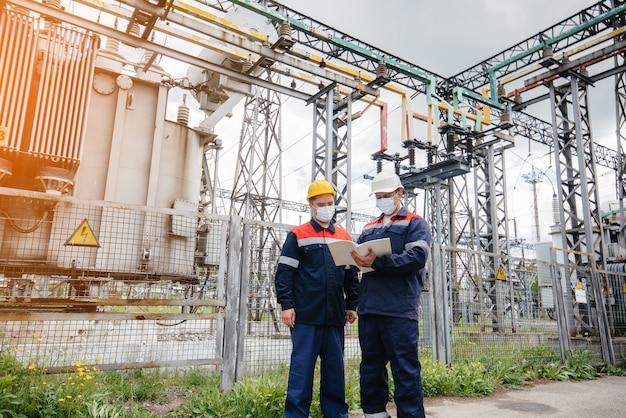 Inżynierskie podstacje elektryczne przeprowadzają przegląd nowoczesnych urządzeń wysokiego napięcia w masce w czasie pandemii wieczorem. energia. przemysł.