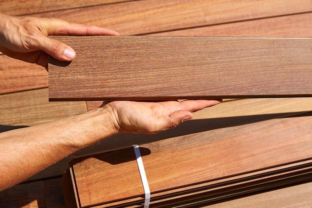 Ipe pokładu instalacja stolarz ręce trzymając drewno