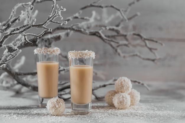 Irish cream lub coffee likier z domowymi, zdrowymi kulkami kokosowymi i płatkami kokosowymi na jasnej powierzchni