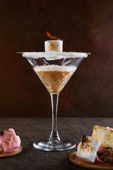 Irlandzki likier śmietankowy w kieliszku do martini z piankami marshmallows z ogniem.