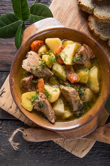 Irlandzki obiad wołowiny mięso duszone z ziemniakami, marchewką i chlebem sodowym na drewnianym stole, widok z góry, miejsce. domowe zimowe jedzenie komfortowe - wolno gotowane