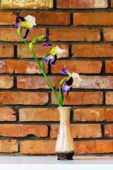 Irysowy kwiat w wazonie na białym stole na tle zbliżenia ściany z cegły