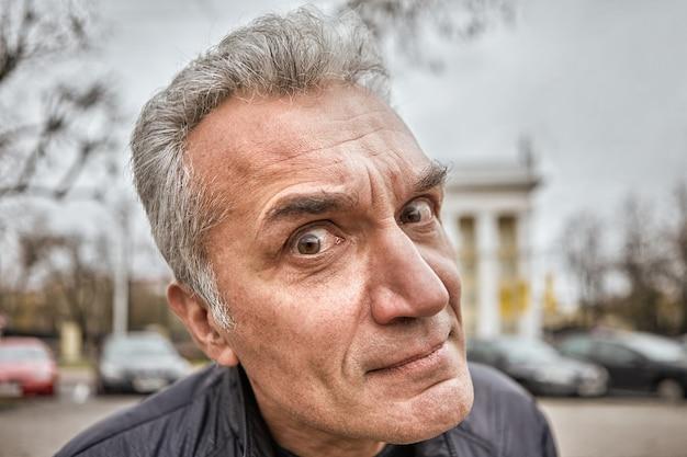 Irytujący mężczyzna w średnim wieku o pytającym spojrzeniu dręczy kogoś na ulicy.