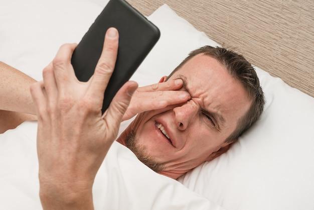 Irytujący smartfon. obudź się. wiadomości spamowe. zaniepokojony śpiący mężczyzna.