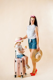 Iść na przygodę. szczęśliwa rodzina przygotowuje się do podróży. mama i córka pakują walizki na podróż.