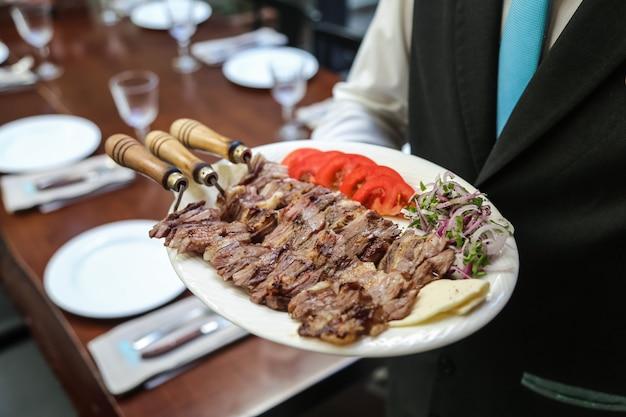 Iskender doner mięso z grilla pomidor ser cebula z widokiem z boku zieleni
