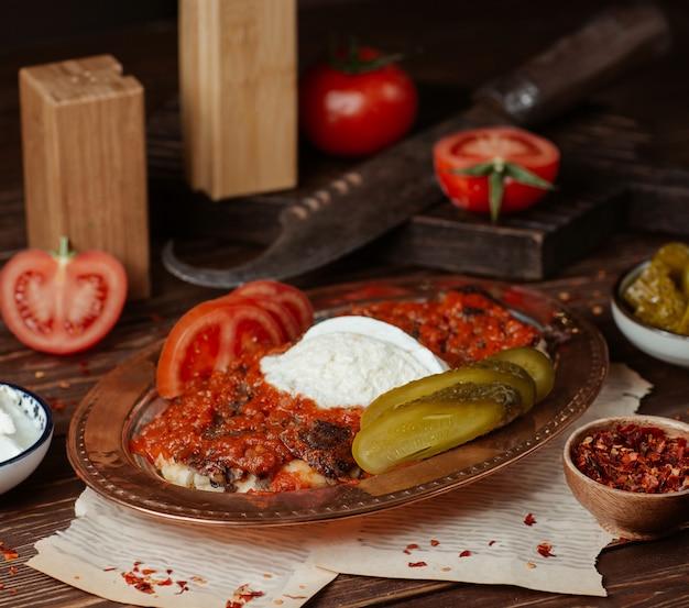 Iskender kebab w sosie pomidorowym z jogurtem i marynowanymi potrawami