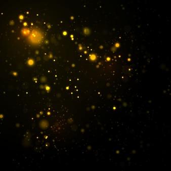 Iskrzaste cząsteczki pyłu na czarnym tle