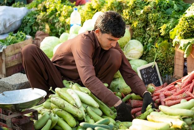 Islamabad, islamabad capital territory, pakistan - 5 lutego 2020 r., młody chłopak sprzedaje warzywa na rynku warzyw.