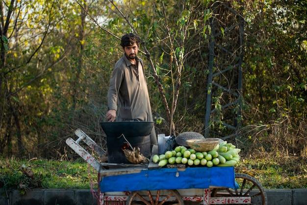 Islamabad, terytorium stołeczne islamabadu, pakistan - 2 lutego 2020 r., młody chłopak piecze świeżą kukurydzę dla klientów.