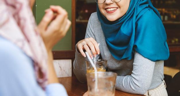 Islamscy kobieta przyjaciele cieszy się i opowiada w sklep z kawą