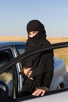 Islamska kobieta kierowca właściciel samochodu przy otwartych drzwiach.