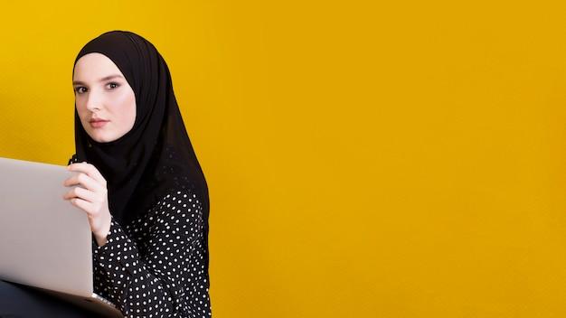 Islamska kobieta patrzeje kamery mienia laptop nad jaskrawym żółtym tłem