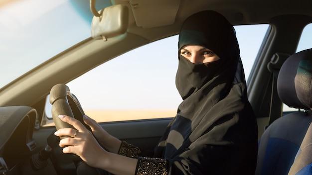 Islamska kobieta w stroju narodowego prowadząca samochód