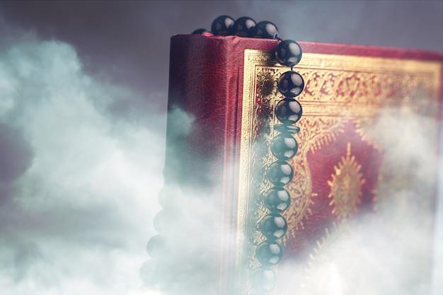 Islamska księga koran z różańcem na szarym tle