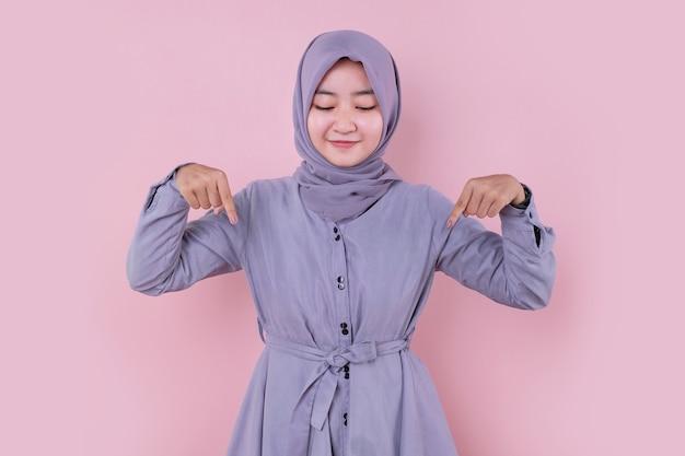 Islamska młoda dziewczyna azjatyckich, wskazując palcami wskazującymi w dół