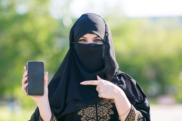 Islamska muzułmanka trzyma w ręku nowoczesny telefon komórkowy