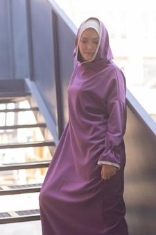 Islamska piękna kobieta w muzułmańskiej sukience stojąca na letnim parku na tle ulicy las jesień ...