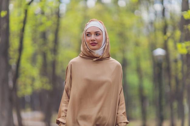 Islamska piękna kobieta w muzułmańskiej sukience stojącej na tle ulicy w parku lato las jesienne drzewa