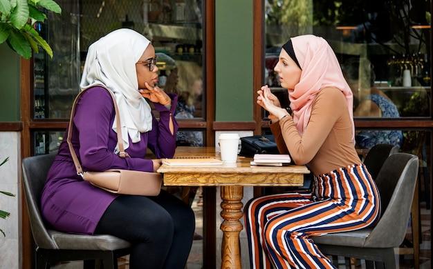 Islamskie kobiety opowiada wpólnie w sklep z kawą