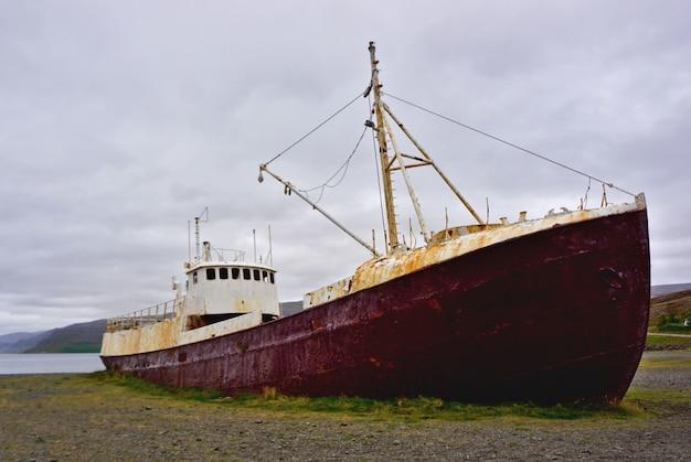 Islandia fiordy zachodnie, patreksfjordur. stary wrak statku na fiordach zachodnich. opuszczony zardzewiały wrak statku w zatoce w północno-zachodniej islandii.