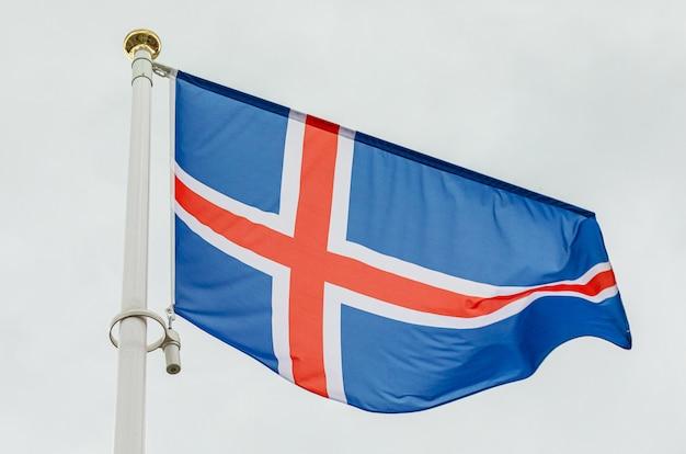 Islandzka flaga macha na wietrze przeciw niebu