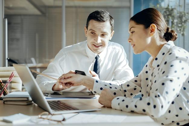 Istotne ulepszenia. przyjemni młodzi koledzy siedzą przy stole i razem przeglądają raport na laptopie