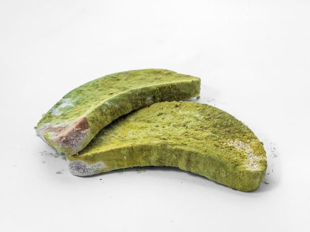 Izolat kawałek chleba pokryty zieloną pleśnią na białym tle.