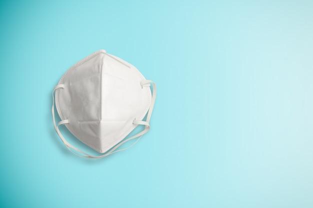 Izolowana biała chirurgiczna maska ochronna do ochrony przed wirusem corona lub covid 19 i pyłem pm 2,5 na niebieskiej ścianie. koncepcja sprzętu opieki zdrowotnej i higieny.