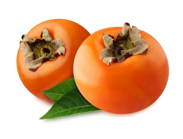 Izolowana persimmon. dwa całe owoce z liśćmi na białym tle na białym tle ze ścieżką przycinającą.