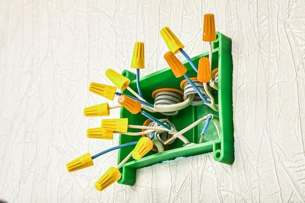 Izolowane elektryczne złącze nakrętki do skręcania przewodów elektrycznych wewnątrz skrzynki przyłączeniowej w okablowaniu domowym.