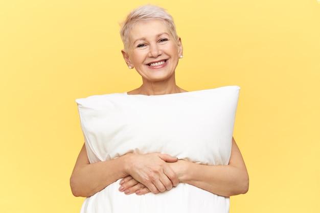 Izolowane obraz wesołej kobiety w średnim wieku z fryzurą pixie stwarzających na żółtym tle na sobie białą poduszkę jako sukienkę, trzymając ramiona wokół niej.