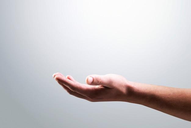 Izolowane tło dłoni pokazujące gest niewidzialnego obiektu