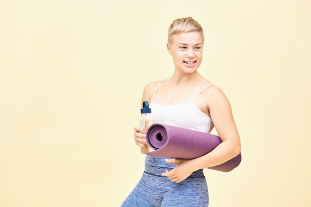 Izolowane ujęcie pięknej, szczęśliwej młodej instruktorki z farbowanymi włosami pixie idącej na trening, niosąc szklaną butelkę jednorazowego użytku z wodą i zwiniętą matą do jogi, odwracając wzrok z szerokim uśmiechem