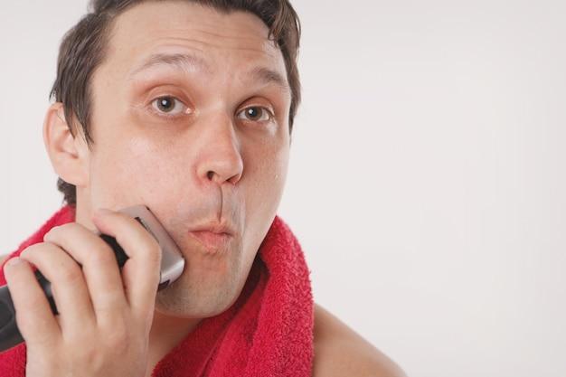Izolowany: mężczyzna goli zarost. facet czyści brodę elektryczną maszynką do golenia. poranne zabiegi w łazience. czerwony ręcznik na szyi. skopiuj miejsce