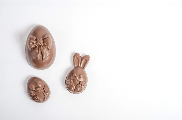 Izoluj czekoladowe jajka wielkanocne w postaci królika i kurczaka na białym tle z miejsca na kopię.