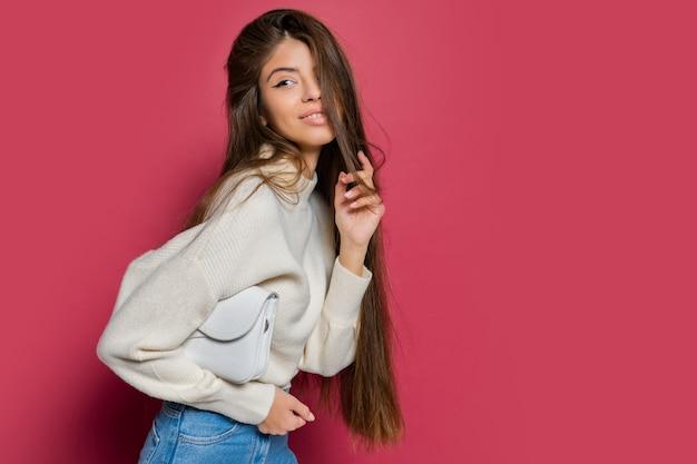 Izoluj piękne długie włosy kobieta w przytulnym białym swetrze i dżinsach pozowanie na różowym tle. trzymająca torebkę ze skóry ekologicznej.