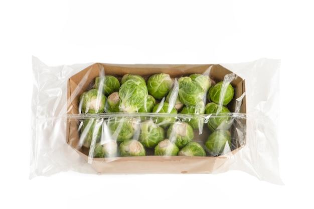 Izoluj świeżą brukselkę w papierowym opakowaniu i przezroczystą plastikową torebkę z brukselką i...