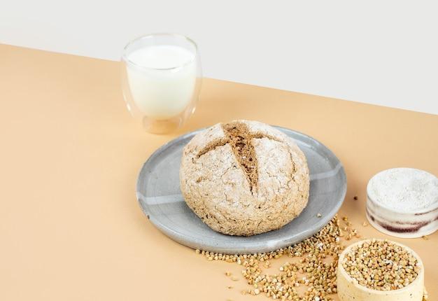 Izometria rzutowania po przekątnej kreatywny beżowe tło z zielonym chlebem gryczanym i ekologicznym mlekiem gryczanym. nieszkodliwe, zdrowe, bezglutenowe zdrowe wypieki. chleb alternatywny. kopiuj spase