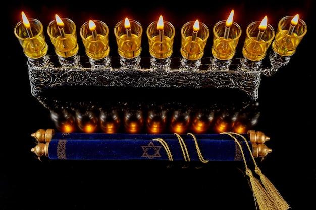 Izraelska menora z palącymi się świecami oliwnymi i torą na chanukę. święto żydowskie.