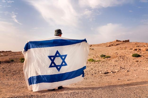 Izraelska piechota wojskowa stoi na środku pustyni trzymając izraelską flagę z gwiazdą dawida. żydowski patriota. turystyczny patriota.
