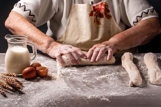 Izraelskie autentyczne jedzenie. staruszka, babcia ręce mieszając proszek do pysznego chleba. surowy chleb chałki